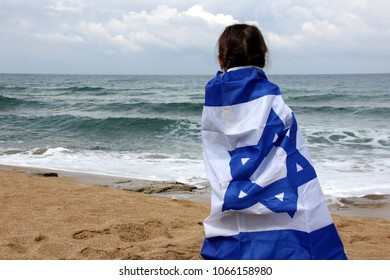 girl with the flag of Israel by the sea