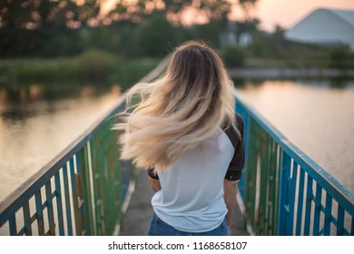 Girl with floating hair on the bridge at sunset