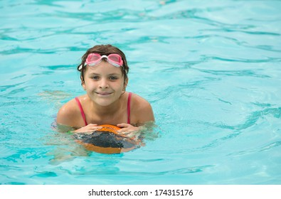 Girl floating on a ball in a swimming pool