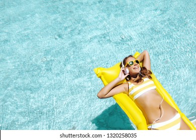 Girl floating on yellow beach mattress and listening to music in earphones in the blue pool. Summer holiday idyllic concept top view.
