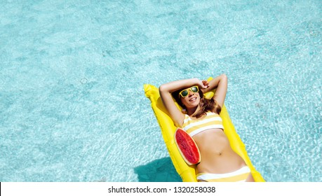 Girl floating on yellow beach mattress and eating watermelon in the blue pool. Tropical fruit diet. Summer holiday idyllic concept top view.