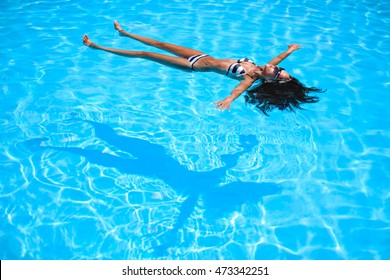 Girl floating in the pool with shadow beneath her