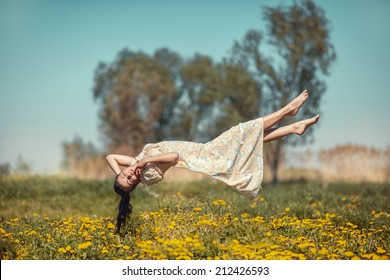Girl floating in weightlessness over the meadow of dandelions.