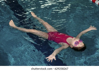 A girl floats on his back in a swimming pool.