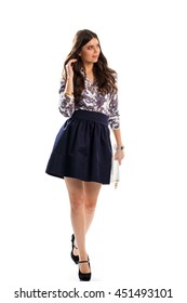 Girl in floral shirt. Navy skirt and white purse. Beautiful model wears spring outfit. High-quality footwear and clothing.