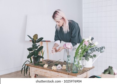 girl florist collects a bouquet of flowers in a white studio