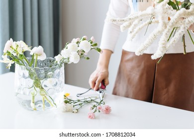 A girl florist makes a bouquet on a white table