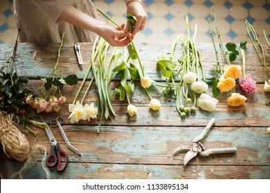 girl florist pruned stems bouquet of flowers. beautiful bright flowers (lilac, roses, daffodil, tulip, hyacinth) and gardener tools on a wooden table in the workshop