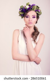 Girl with flower crown posing in studio, white background, portrait