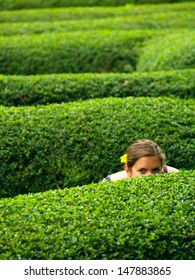 A girl with a flower in her hair, hiding in a maze