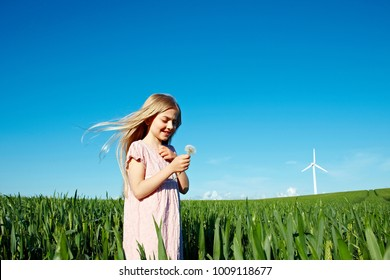 Girl with flower standing in field
