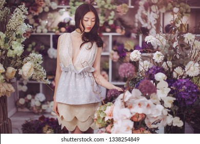 Girl in flower store. Woman standing against floral bokeh background in floral shop. Joyful asian female. Playful fashion model looking at camera and smiling.