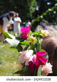 A girl with flower wrath watching the installation of the midsummer pole at midsummer festivities 2018