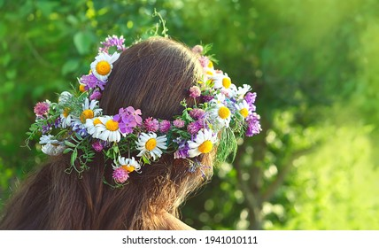 girl in flower wreath outdoor, rear view. Floral crown, symbol of summer solstice. traditional Slavic ceremony on Midsummer, wiccan Litha sabbath. pagan holiday Ivan Kupala - Shutterstock ID 1941010111