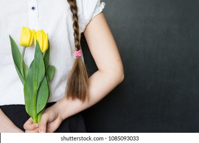 Girl with flowers against blackboard celebration mothers day background concept
