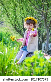 Girl with flowers of dandelions. Selective focus.