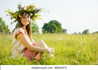 girl in flowers wreath and traditional clothes sitting  on meadow