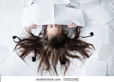 A girl with flowing hair and figures of musical notes lies on her back among clean sheets of paper. Half the face and fingers are visible