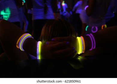 Girl with fluorescent bracelet relaxing on couch during a party