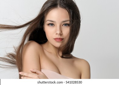 Girl with fluttering hair. Beautiful woman with bare shoulders has a clean well-groomed skin and long straight hair. Close-up portrait against a light gray background.
