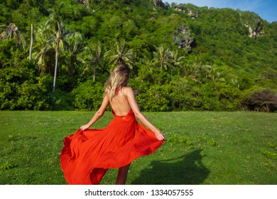 girl in a fluttering red dress walks on the green grass barefoot, against the background of tropical palm trees, the face is not visible