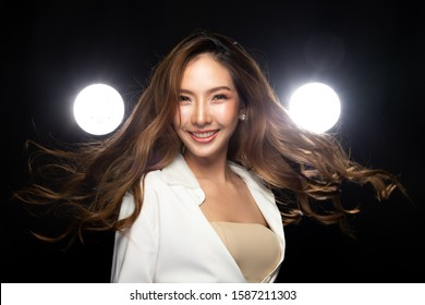 Girl is flying and throwing windy curl hair around.  Beautiful Asian Woman flutters blonde Brown dying color hair style in the air, smile and spin around over dark background with two backlit.