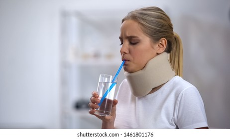 Girl in foam cervical collar trying to drink glass water with straw poor attempt