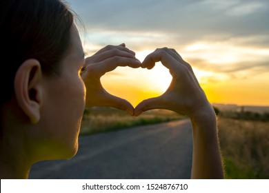 girl folds her arms in the shape of a heart against the sky