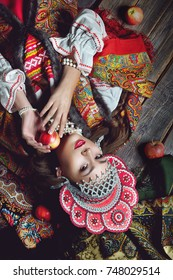 The girl in the folk style and bright make-up holding an Apple on dark wooden background top view