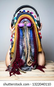 Girl is fooling around in the winter while waiting for the summer and jokingly made a funny mask of multicolored scarves in the shape of rastaman face with dreadlocks. Concept of carefree happy life.