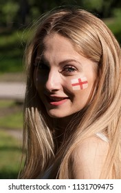 Girl football cheerleader with a painted flag of Britain on her face. England. Uk.
