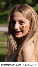 Girl football cheerleader with a painted flag of Belgium on her face.