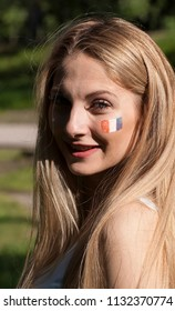 Girl football cheerleader with a painted flag of France on her face.