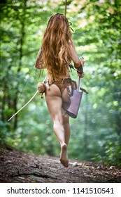 Girl forest hunter with bow and arrow running in the woods