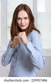 Girl in formal attire is standing in a pose of a boxer