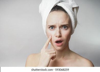 girl found acne on her face. surprised face.Trying remove