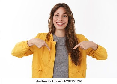 Girl found what you search. Attractive cheerful smiling happy young female student pointing down index fingers sharing awesome offer grinning toothy feel upbeat found excellent promo copy space