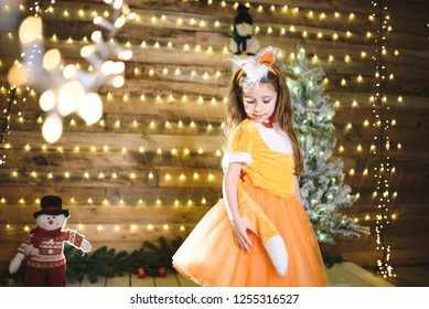 girl in fox dress looking at tail at christmas tree