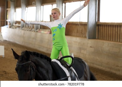 girl is free kneeing on a black horse