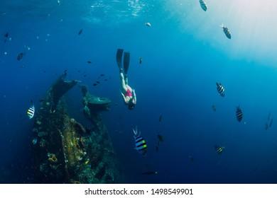 Girl freediver swimming with fins at Liberty wreck ship. Freediving in blue ocean