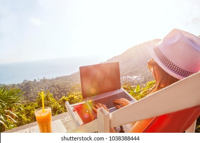 Girl freelance work typing on laptop and looking at monitor screen desktop with beautiful view background and cocktail outdoors sun sky and greens. Traveling with a computer concept. Place for text