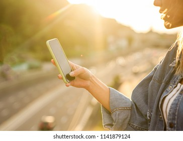 girl freelancer at sunset speaks on the phone and works