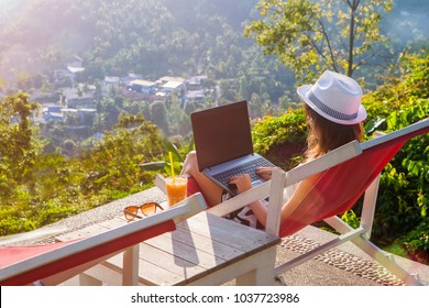Girl freelancer work typing on laptop and looking at monitor with beautiful view and cocktail outdoors sun sky and greens. Traveling with a computer. Online dream job on the island in Thailand concept