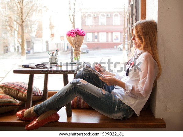 Girl freelancer working in a cafe remotely, draws a project, a business talk in front of the window against the sun.