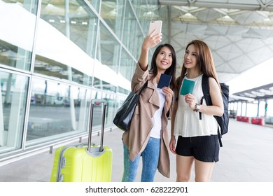 Girl friends go for a trip together and taking selfie in airport