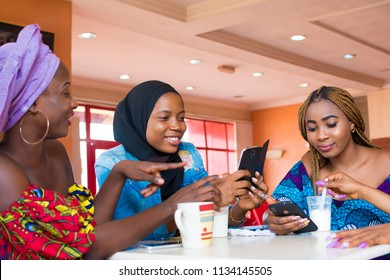 girl friends hanging out together in a fast food restaurant viewing something on a phone and laughing while enjoying ice cream