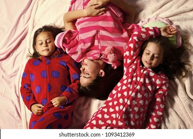 Girl friends in pajamas sleep in bed, top view. Good night, napping, bedtime, slumber, dream, sleepover concept