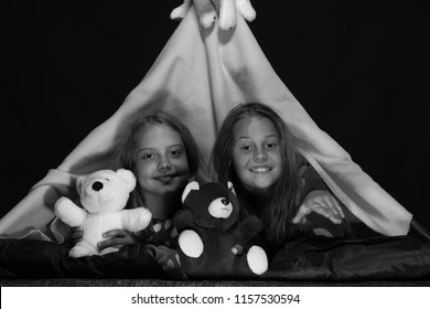 Girl friends playing with toys in blanket tent. Kids wearing red jammies in  bed on 4ff3e3726