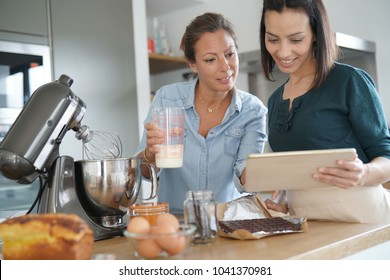 Girl friends preparing cake together with pastry robot
