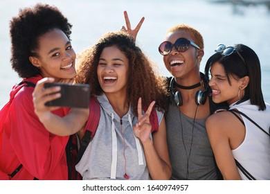 Girl friends taking photo using smartphone laughing happy group of women having fun posing for mobile phone camera enjoying summer